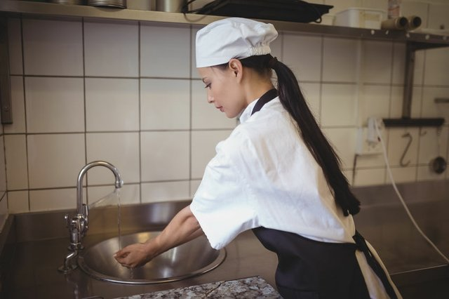 Female chef washing hands in the commercial kitchen